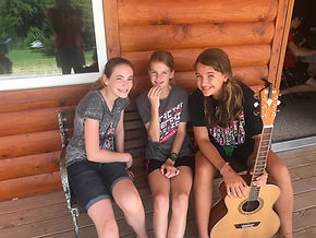 Three campers in front of a cabin posing with a guitar