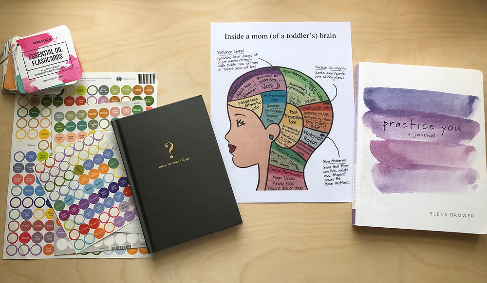 Flat lay photography of toddler mom brain, essential oils, practice you journal, feelings flash cards + idea ledger