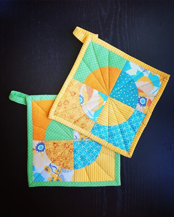 Photo of quilted pot holders in yellow, aqua, green, and orange.