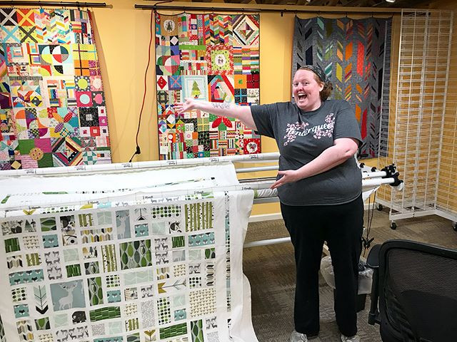 """Photo of a red haired woman in a shirt that says """"tenderqueer"""" standing in front of a long arm quilting machine, in front of several quilts. A quilt is on the long arm machine, and the woman is gesturing to it excitedly."""