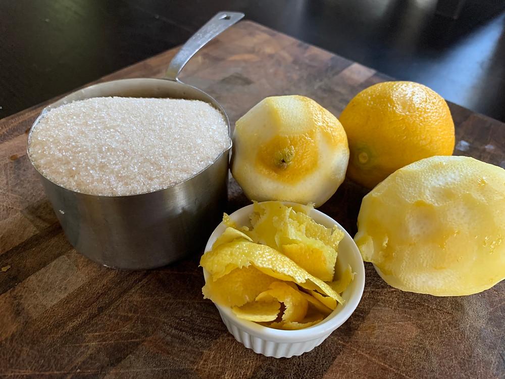 Photo of sugar, lemon peel, and partially peeled lemons sitting on a wood cutting board