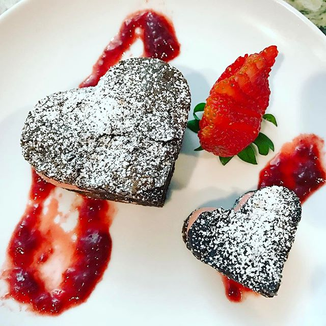 Valentine's Day dessert! Stacked brownie sandwich hearts, layered with strawberry buttercream, plate