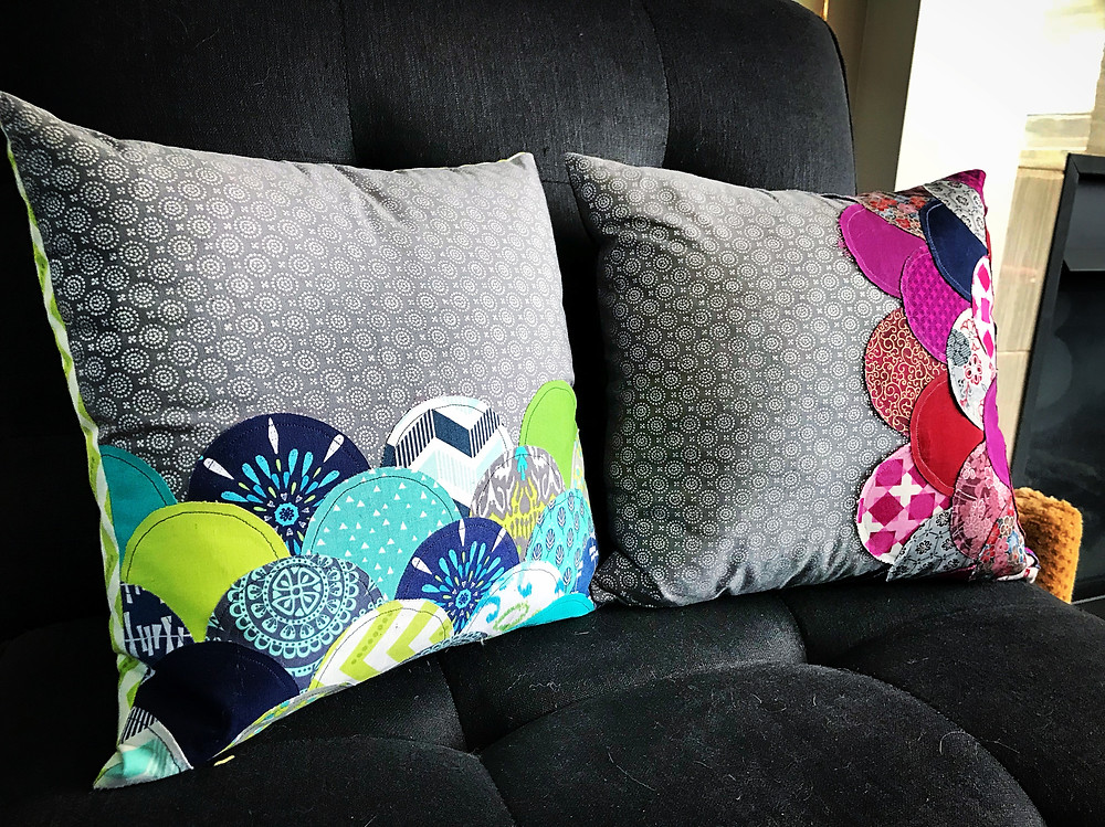 Photo of two pillows next to each other on a black chair. The pillows both have grey backgrounds with silver medallion shapes and are overlayed with rows of overlapping half circle shapes in various colors. One pillow uses a teal, lime, and navy color scheme, and the other uses red, fuschia, plum, and navy.