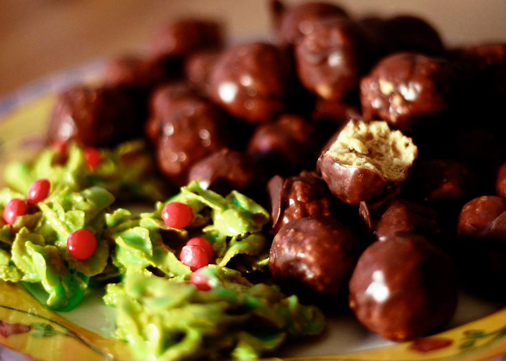 Photo of chocolate-coated candy balls on a plate with some holly-shaped cookies