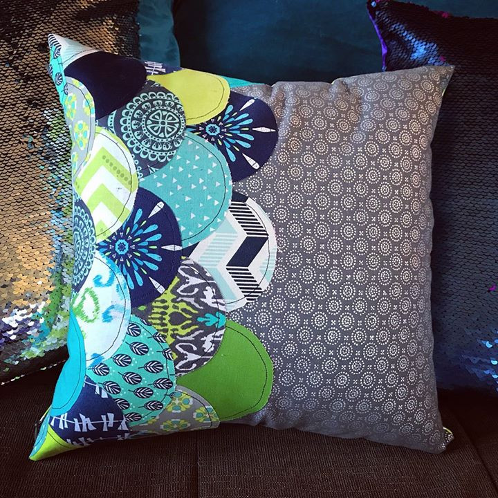 Photo of a homemade green, teal, and navy blue pillow with curved, overlapping pieces of fabric arranged in rows and layered on top of each other.