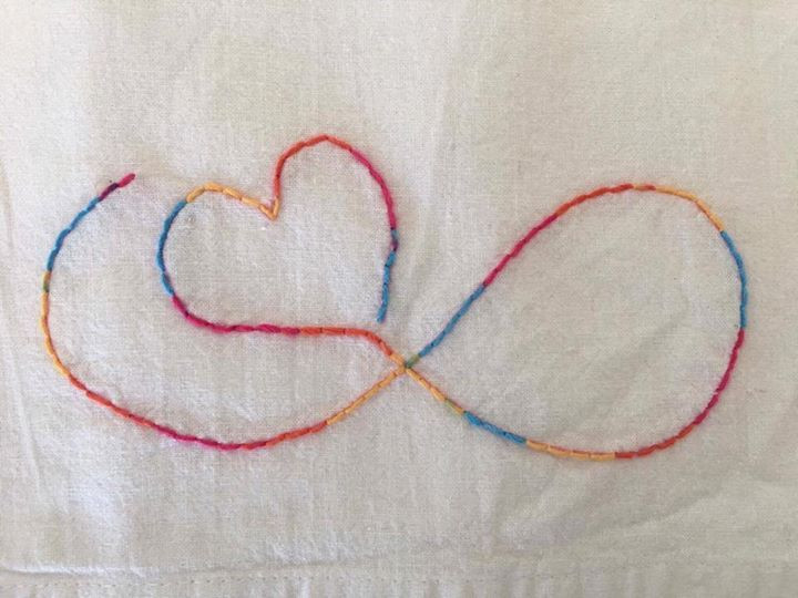 Photo of embroidery on a towel. The design is an infinity symbol combined with a heart. The infinity symbol starts at the left, goes to the right to make a loop, and ends in the upper left again with a heart. The thread is rainbow colors.