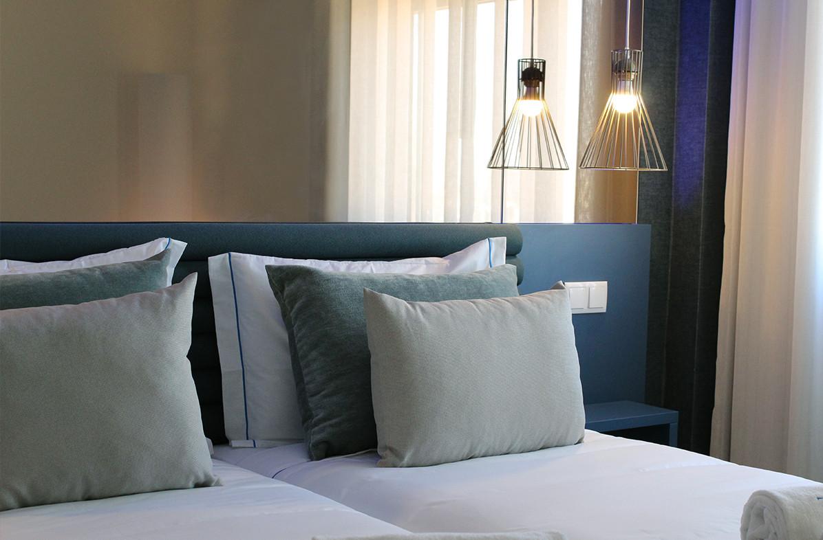 quarto de hotel com cama em tons de azul e verde àgua