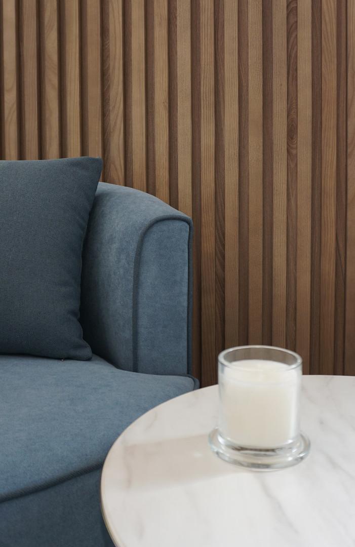 Detalhe ripado de madeira e sofá azul