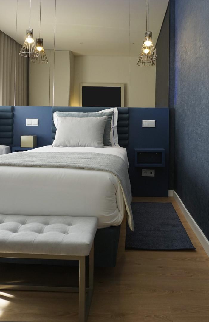 Quarto duplo de hotel com cabeceira estofada a tecido e banqueta