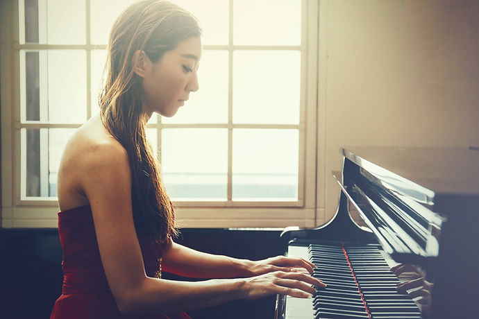 Asian woman playing piano in window back