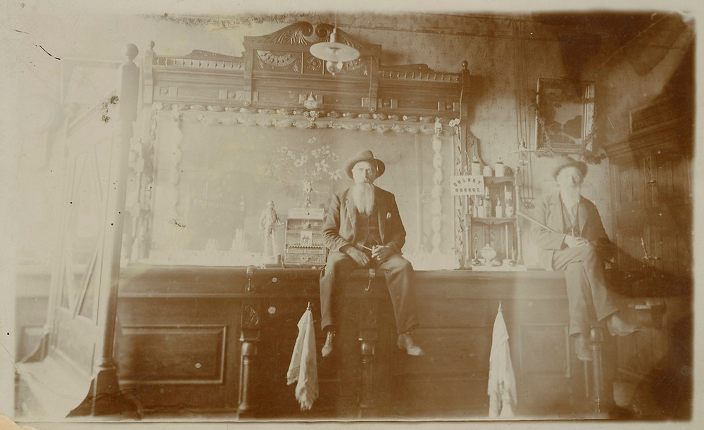Black and white photo of two men sitting on a bar. created by Breckenridge Heritage Alliance.