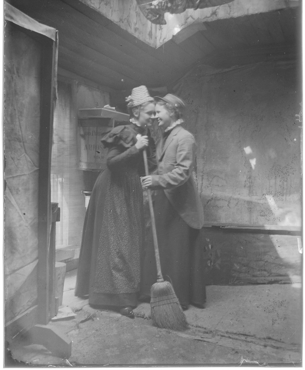 Image created by Breckenridge Heritage Alliance. Black and white photo of two people holding a broom smiling