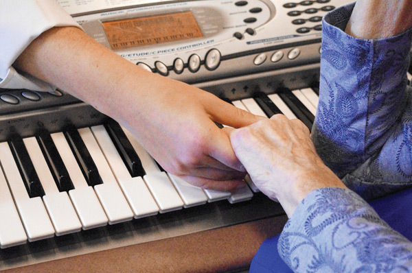 elderly women holding hands on piano