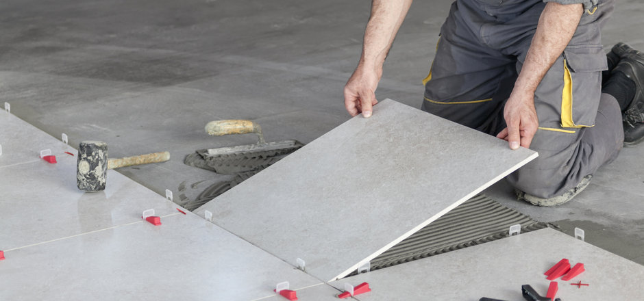 Ceramic Tiles. Tiler placing ceramic wal