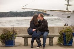couple engagement kissing on bench