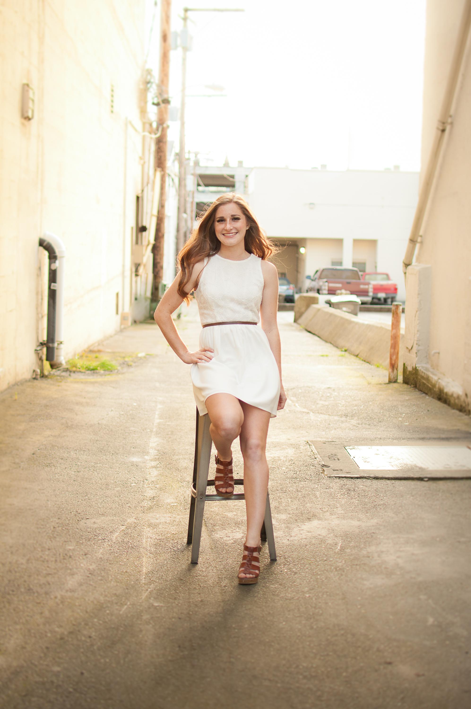 Senior girl on stool in alley