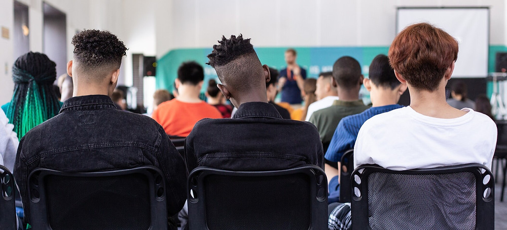 3 Young men sat, listening to someone give a speech