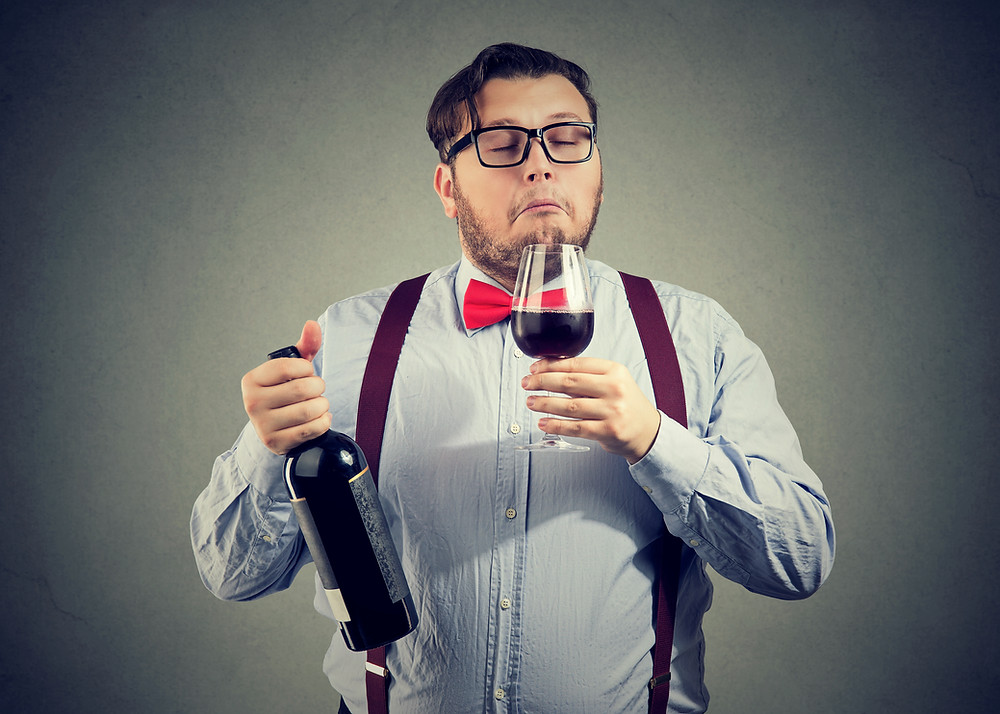 A guys testing a glass of wine, sommelier toronto