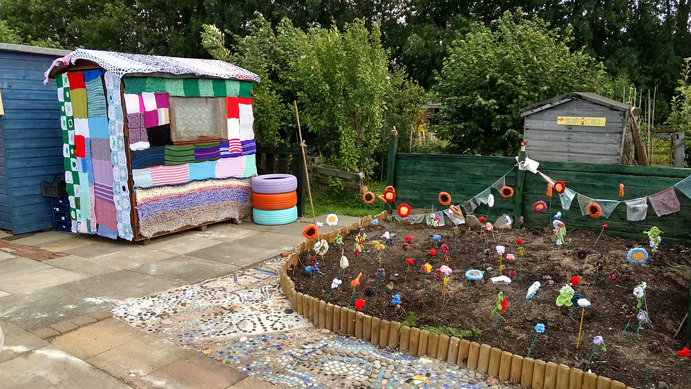 Yarn bombed shed and wild flower bed in the Community Plot