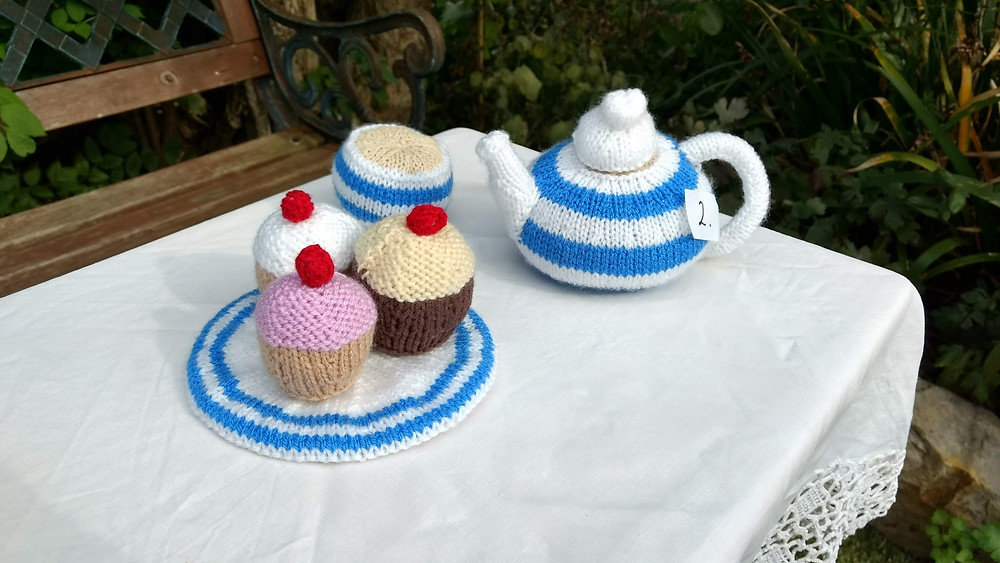 Knitted teapot, knitted cup of tea and knitted cakes
