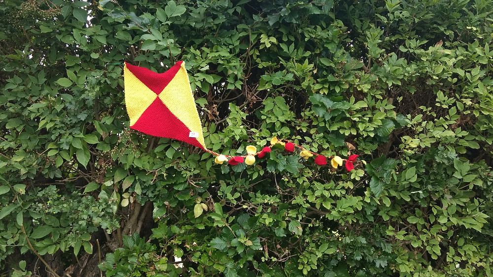 Knitted kite caught in a hedge