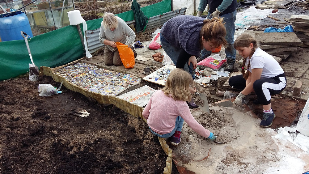 children helping make the mosaic path