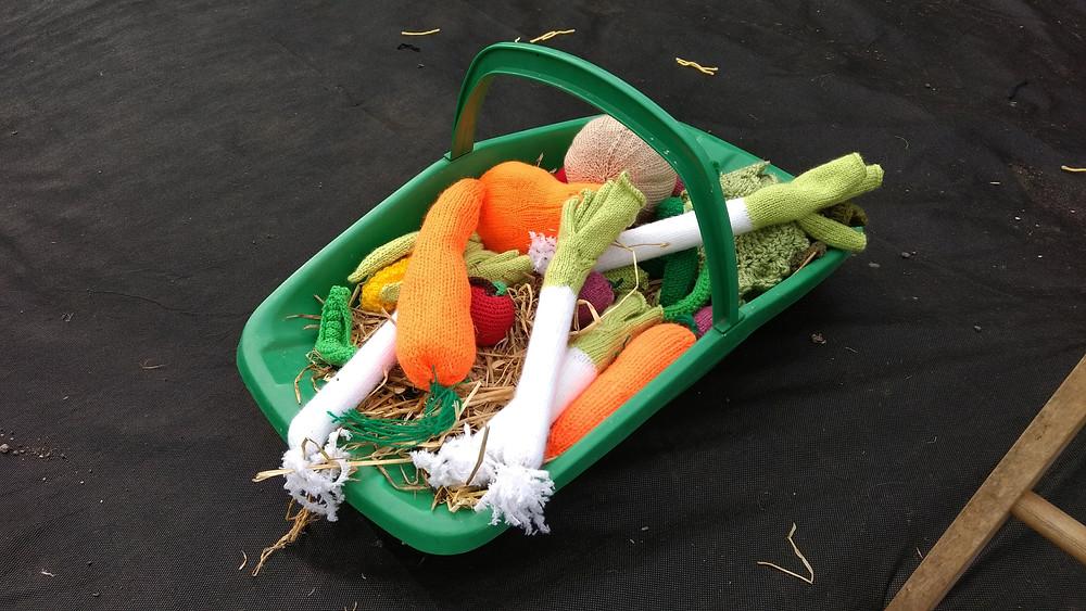 Plastic trug full of knitted vegetables