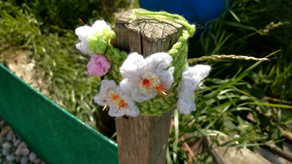knitted flower on a fence post