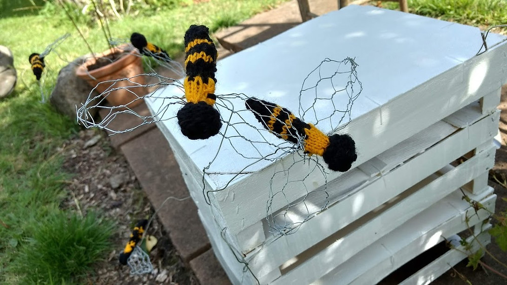 Knitted bees buzzing around a beehive