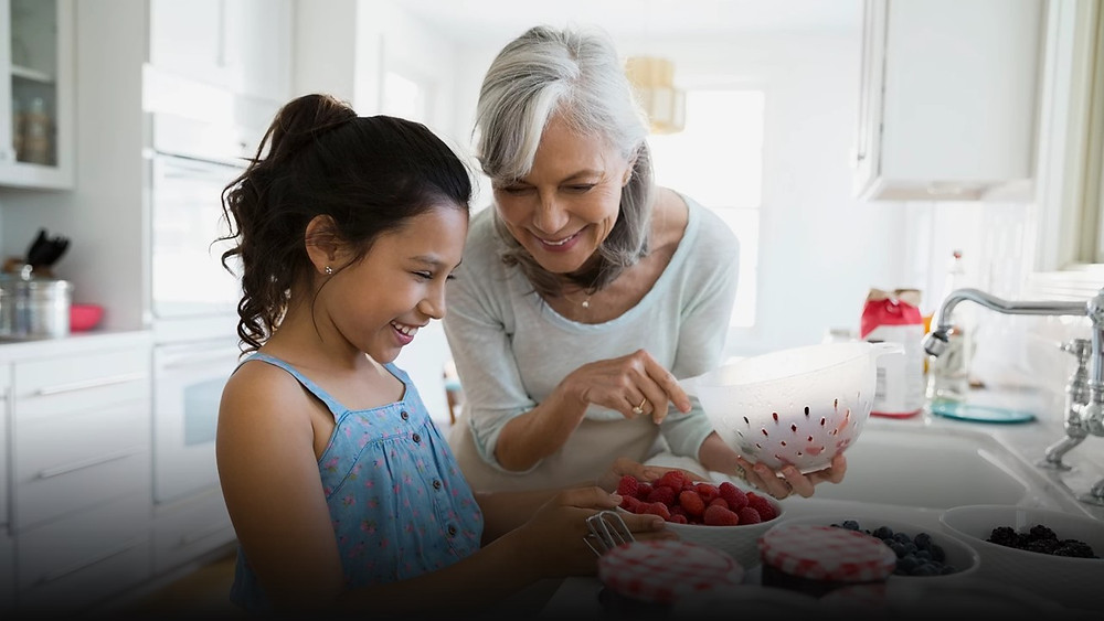 Grandmother washing berries with granddaughter at sink in whits kitchen