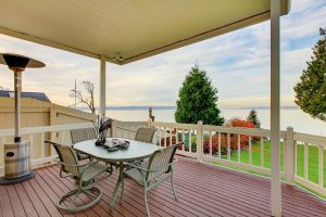 water view from the covered wooden deck with white railings. Luxury two story house exterior.