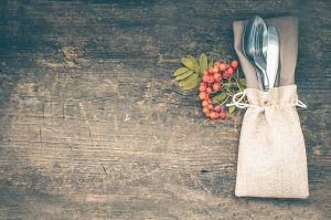 Thanksgiving autumn place setting with cutlery on wooden background.