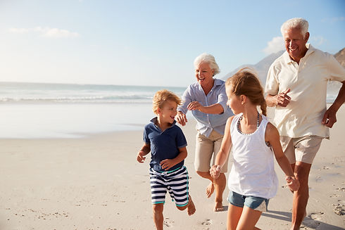 Grandparents Running Along Beach With Gr