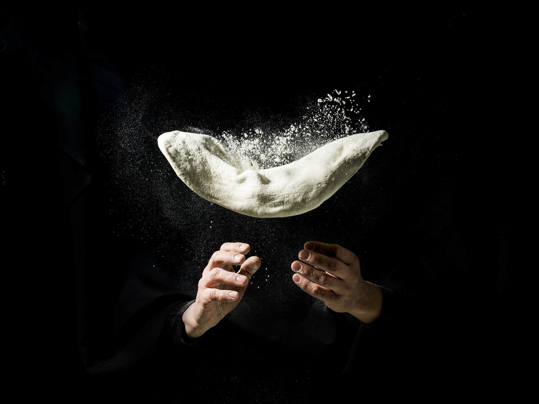 flying pizza dough with flour scattering