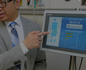 Person in a suit interacting with XSENSOR's ForeSite PT Patient Turn system user interface.