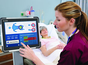 A nurse monitors a patient's skin using XSENSOR's ForeSite PT Patient Turn system while the patient lays in a hospital bed.