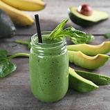Fresh avocado smoothie with slices on wo