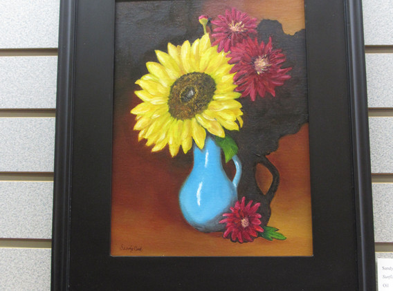Framed painting of a vase of colorful flowers.