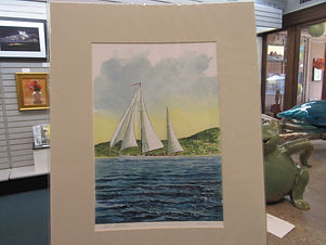 Matted print of a sailboat on a lake.