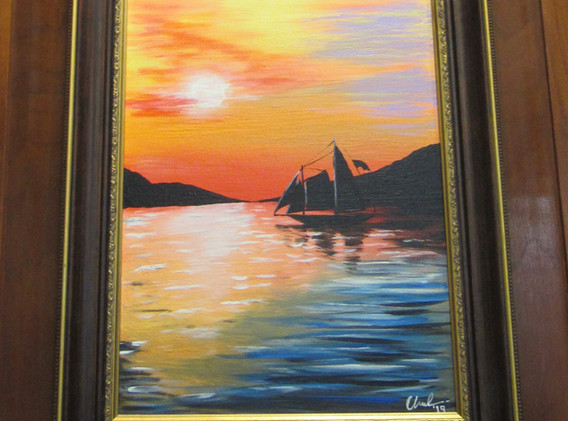 Framed painting of a coloful sunset and a sailboat on a lake.