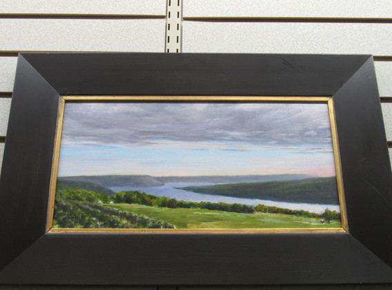 Framed photos of a lake and green hills.