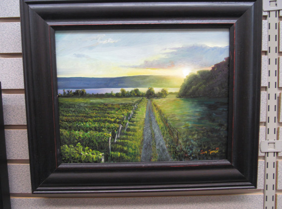 Framed painting of a sunny vineyard.