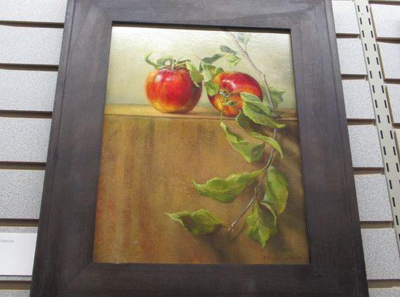 Framed painting of apples and a tree branch.