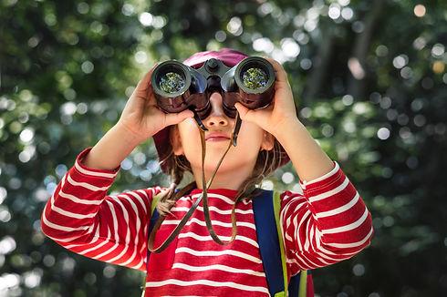 Little girl using binoculars in the fore