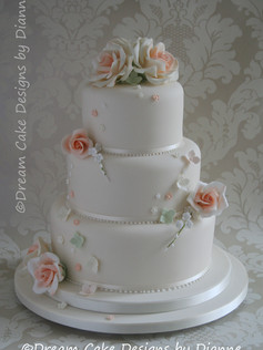 'CATHERINE' ~ stylish 3 tier white wedding cake with peach coloured roses with scattered blossoms