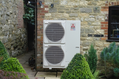 Air source heat pump at the back of a house.