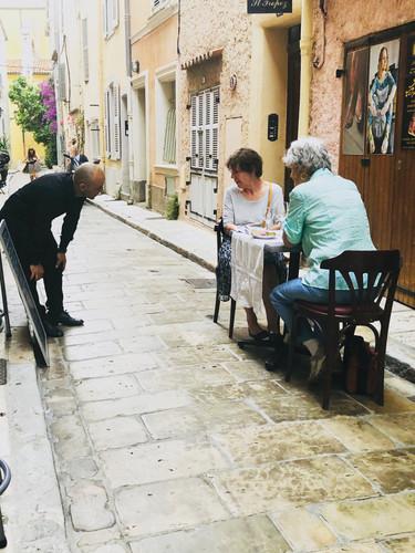 Kellner, der 2 Damen die Speisekarte offeriert .jpe