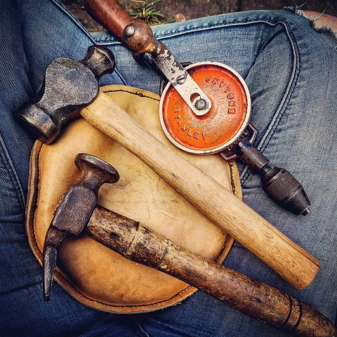 A selection of old tools including two hammers, a hand drill and sandbag.