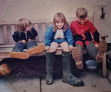 Kim sat on a bench age four.