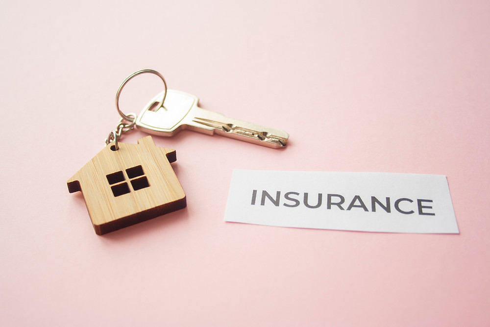 gold key on wooden house-shaped keyring with word INSURANCE on paper